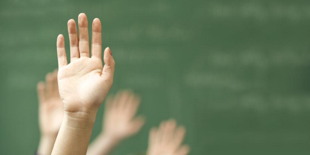 Hands raised in classroom
